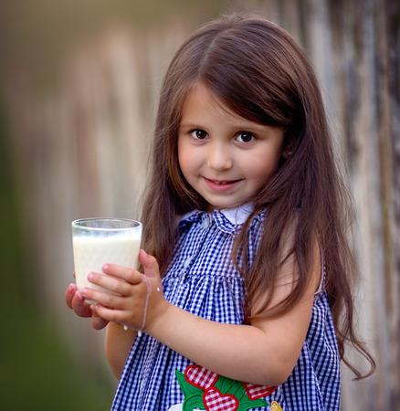 Cute little beautiful girl with milk Фото со стока