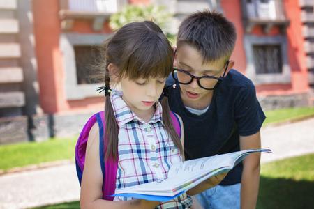 Schoolchildren reading the book near the school