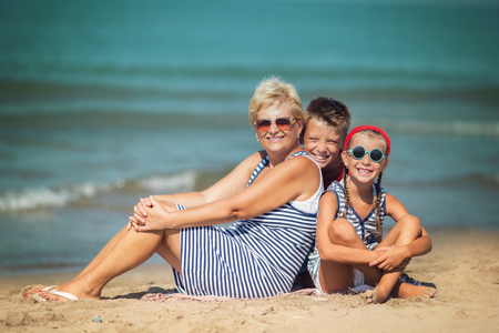 Summer holiday. Grandmother with grandchildren are walking on the sea beach