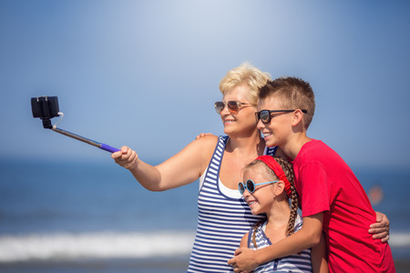 Summer holiday.Grandmother with grandchildren taking selfie on the beach Фото со стока