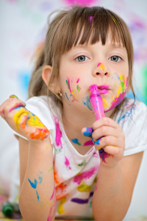 Portrait of a cute cheerful happy little girl showing her hands painted in bright colors Фото со стока