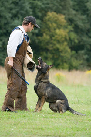 german shepherd on the grass: The figurant training a German shepherd. Attack to a sleeve Stock Photo