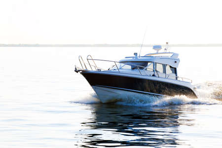 boat: A covered powerboat speeding through the water