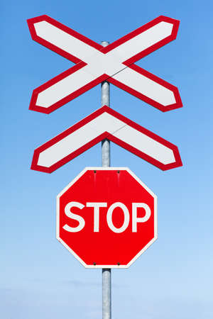 Stop and Railway crossing signs over blue sky background photo