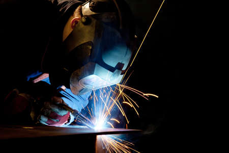 man with mask welding at steel construction at workshop photo