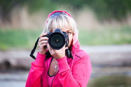 beautiful young women in pink with digital camera Stock Photo