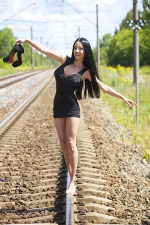 Beautiful Young Woman Walking in Balance on Railway Tracks Stock Photo - 41611132