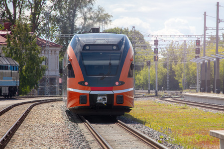 High speed orange train on the railway station at bright day
