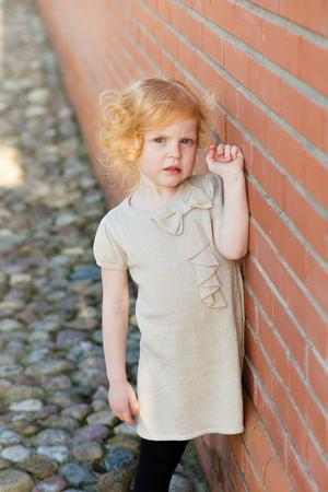 harming: portrait of a cute little redhead girl in city