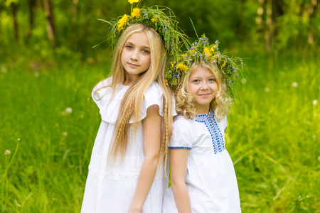 Beautiful cute blonde girl with wreath of flowers outdoors in summer