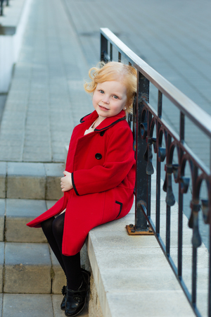 harming: portrait of a cute little redhead  girl in red coat sitting on the stairs Stock Photo