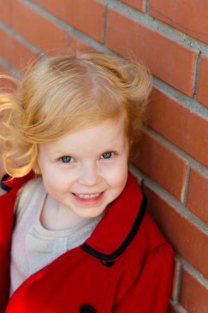 harming: portrait of a cute little redhead girl in city