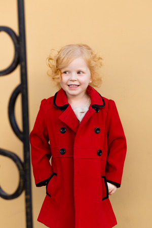 harming: portrait of a cute little redhead  girl in red coat standing by the wall Stock Photo