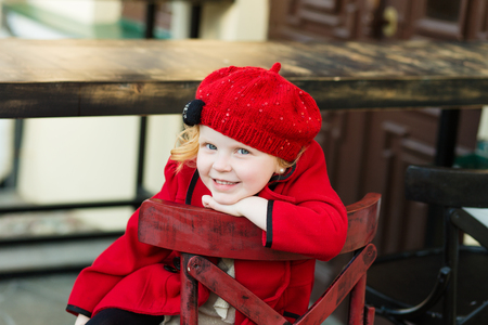 gir: portrait of a cute little redhead girl in city in a red cap sitting on a high chair Stock Photo