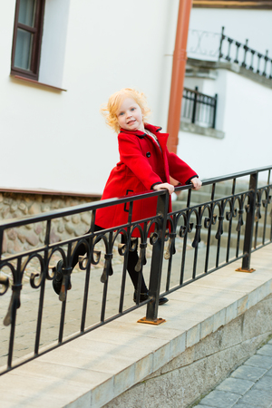 gir: portrait of a cute little redhead  girl in red coat outdoors in summer
