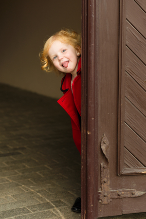 harming: portrait of a cute little redhead  girl in red coat showing tongue