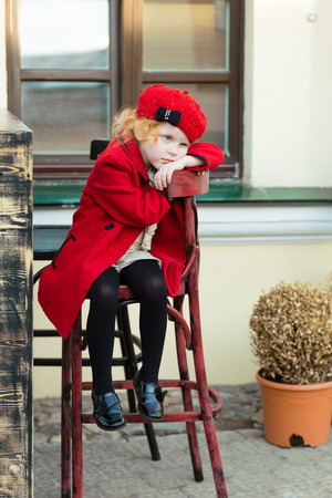 harming: portrait of a cute little redhead girl in city in a red cap sitting on a high chair Stock Photo