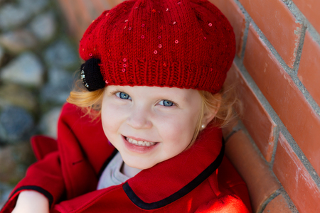 harming: portrait of a cute little redhead girl in city in a red cap