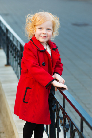 harming: portrait of a cute little redhead  girl in red coat outdoors in summer