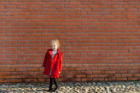 harming: portrait of a cute little redhead girl in city at the wall
