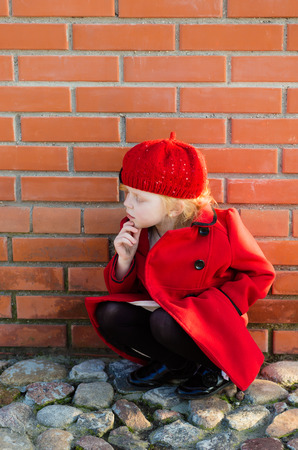 harming: portrait of a cute little redhead  girl in city in a red cap sitting at the wall