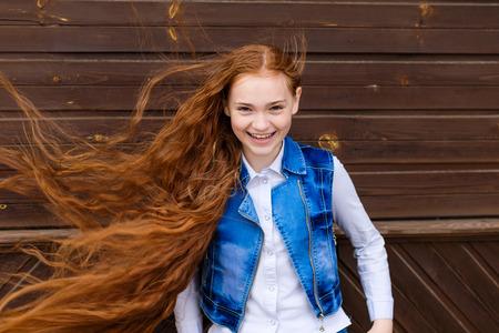 Portrait der schönen lächelnden rothaarige Mädchen mit langen Haaren im Wind flattern