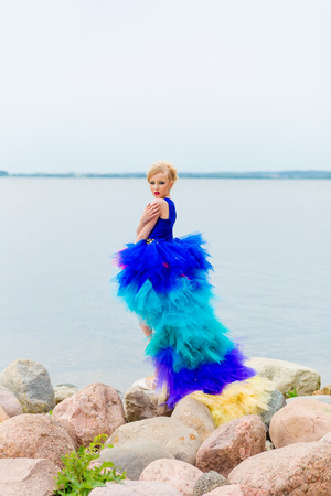Portrait of a beautiful girl in a blue dress standing on the beach in pointe Imagens