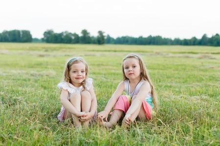dos amigas hermosas que se sientan en el prado