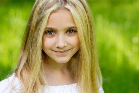 Portret van een mooi blondemeisje in openlucht in de zomer