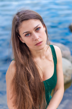 green eyes: portrait of a beautiful sad girl with green eyes outdoor in summer