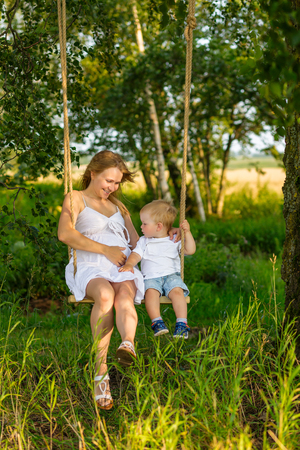 position d amour: A little boy with his pregnant mother sitting on a swing. Pregnant mom with a boy resting in a meadow. Mother and son outdoors in summer