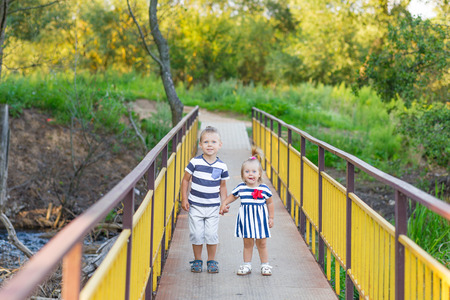 Brother and sister holding hands. Children on the bridge.