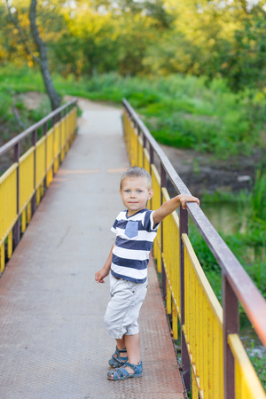 Cute boy with blue eyes posing on a golden bridge to the outdoors in summer
