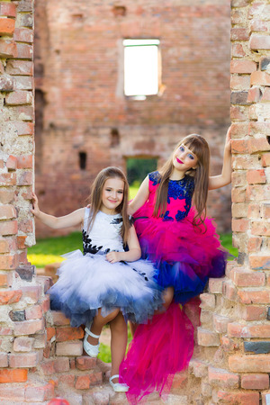 vibrance: Fashion photo of two beautiful girls in color dresses on the background of brick ruins