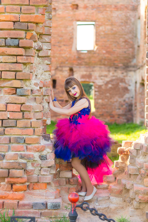 vibrance: fashion photo of a beautiful girl in a color dress on a background of brick ruins