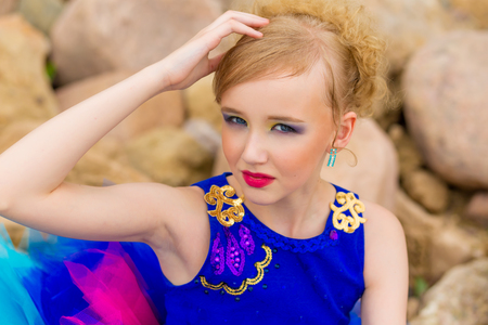 portrait of a beautiful cute girl with makeup in a blue dress