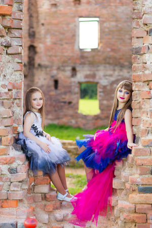 Fashion photo of two beautiful girls in color dresses on the background of brick ruins