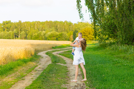 position d amour: Pregnant mom with a boy resting in a meadow. Mother and son outdoors in summer
