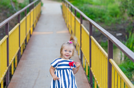 Cute little girl with blue eyes posing on a golden bridge to the outdoors in summer Stock Photo