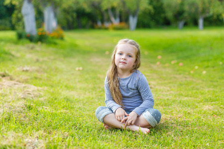 sitting on the ground: Portrait of a cute girl with long blond hair on nature Stock Photo