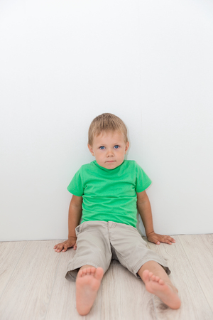 messing: Little handsome boy with blue eyes sitting on the floor and looking at you