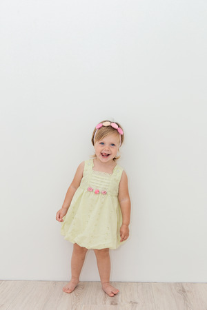 Beautiful little girl in a pretty dress standing near the wall of house Stock Photo