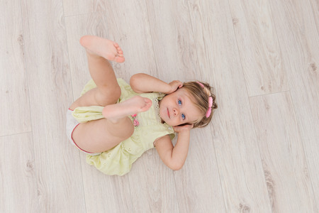 Little handsome girl with blue eyes lying on the floor and looking at you