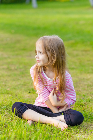 sitting on the ground: Portrait of a cute girl with long blond hair sitting on the ground
