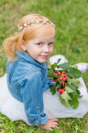 Portrait of a cute little pin-up girl on the nature. Portrait of a beautiful redhead child with a sweet smile. The charming redhead kid Stock Photo