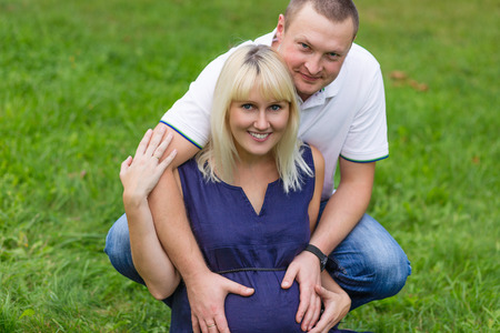 brooding: Young pregnant mother with her family in a park. Family resting in a nature. Pregnancy