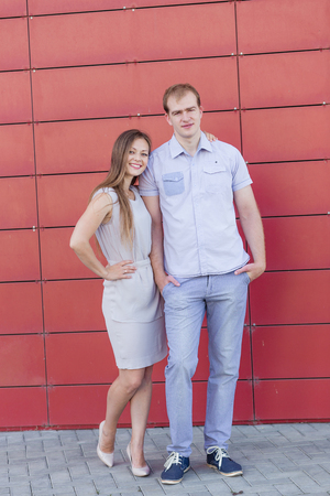 he she: Portrait of happy guy and girl on red background
