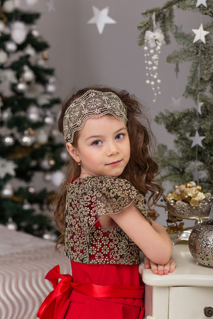 threshold: Little beautiful girl in a red evening dress the Christmas tree. Girl in red in Christmas decorations. Cute child on the bed