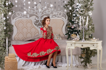 pine wreaths: Beautiful girl in red long dress at the Christmas tree. A young girl is preparing for the new year.