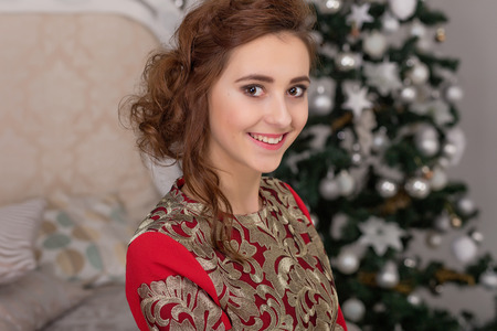 Beautiful girl in red long dress at the Christmas tree. A young girl is preparing for the new year.